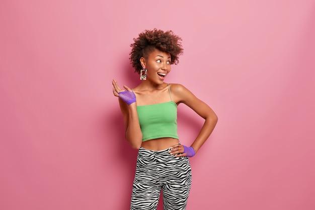 La donna dalla pelle scura e contenta sportiva tiene la mano sulla vita, vestita con top corto e leggings, indossa guanti sportivi, ride allegramente, guarda da parte