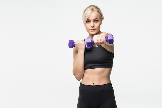 Sporty pretty blonde young girl with fit muscular body works with dumbbells in studio on white