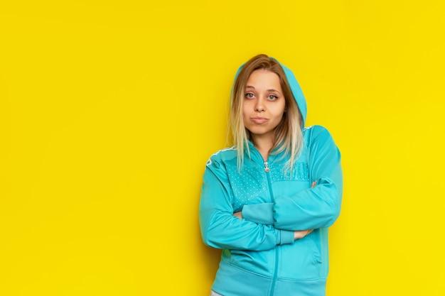 Спортивная довольно уверенная кавказская молодая блондинка в бирюзовой спортивной куртке с капюшоном стоит со скрещенными руками, изолированными на ярко-желтой стене.