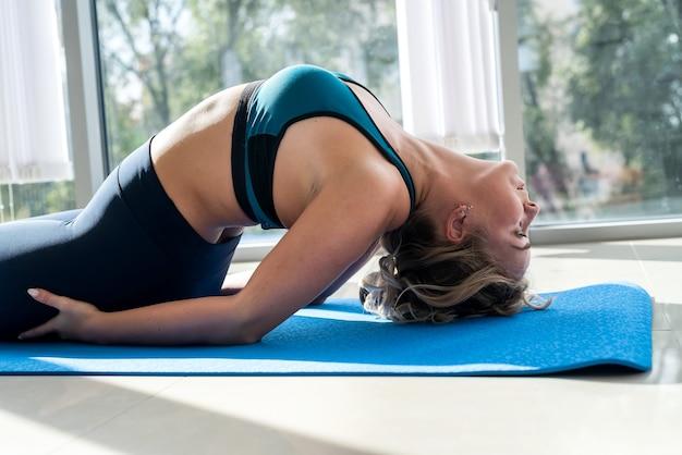 床に横たわってアーサナを練習し、自宅でヨガの練習をしているスポーティなかわいい女の子。健康的なライフスタイルのためのレクリエーション