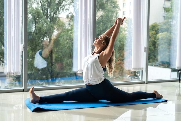 Спортивная красивая девушка, лежащая на полу, практикующая асаны, упражнения йоги дома. отдых для здорового образа жизни