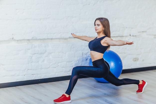 La donna sportiva e carina ha un equilibrio, facendo esercizi di yoga in palestra bianca