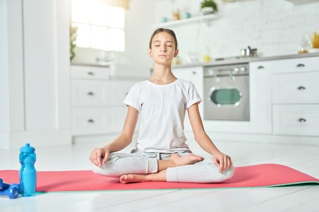 운동복을 입고 요가를 연습하는 스포티한 히스패닉 10대 소녀가 부엌에 있는 매트에 로터스 포즈를 취하고 있습니다. 홈 인테리어 배경입니다. 건강한 생활 방식, 집 개념을 유지하십시오. 전면보기
