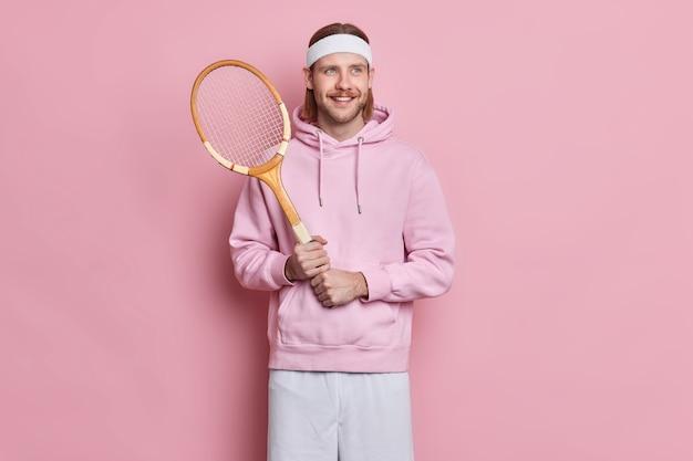 口ひげを生やしてスポーティな満足のアクティブな男は、余暇の間に好きなゲームを楽しんでテニスラケットを保持します