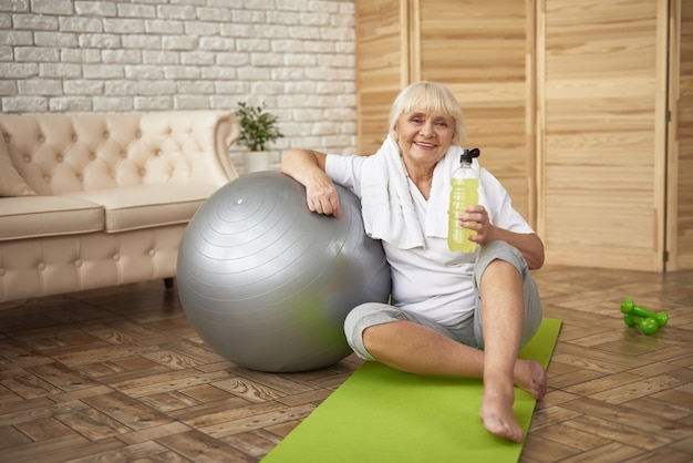 Sporty senior lady drinks vitamin water workout