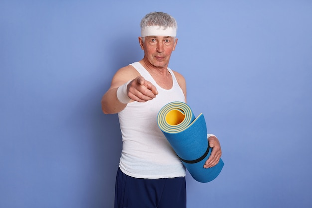 Sporty senior white haired man holding yoga mat, looking and pointing at front