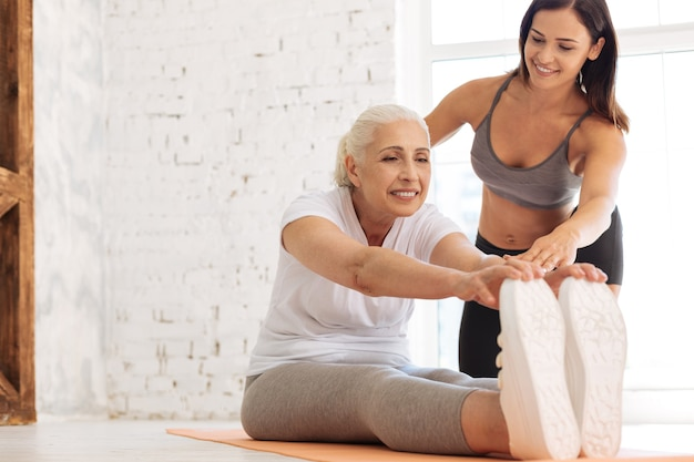 Sporty senior woman keeping smile on her face and sitting near her instructor while putting fingers on the trainers