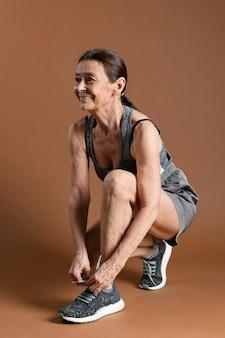 Макет спортивной пожилой женщины в спортивной одежде, завязывающей шнурки