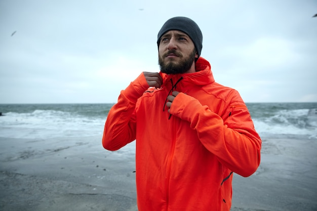Sporty serious looking young dark haired bearded man with eyebrow piercing wearing black cap and winter sporty coat with hood, posing over coastline of sea on cold stormy weather