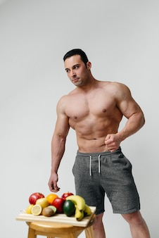 明るい果物と白い壁にポーズをとってスポーティなセクシーな男。ダイエット。健康的なダイエット。