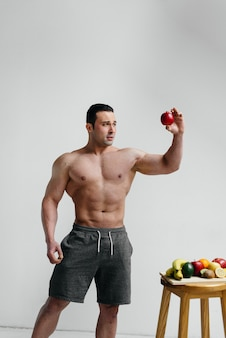 Sporty sexy guy posing on a white background with bright fruits. diet. healthy diet.