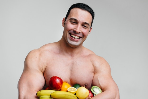 Sporty sexy guy posing on a white space with bright fruits. diet. healthy diet.