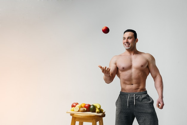 Sporty sexy guy posing on a white with bright fruits. diet. healthy diet.