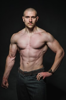 Sporty sexy man stands topless on dark. sports, beauty.