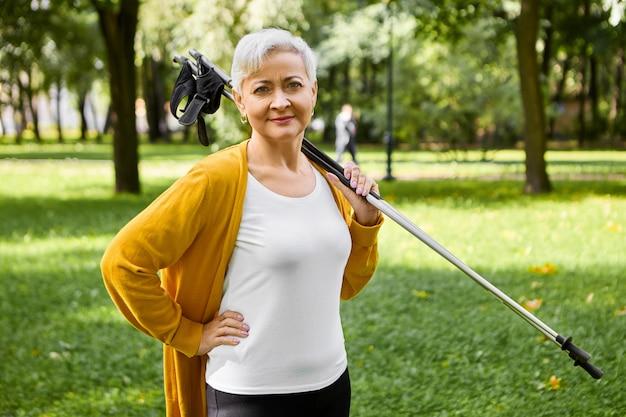 건강한 활동적인 라이프 스타일에 예라고 말하는 은퇴 한 스포티 한 짧은 머리의 여성, 어깨에 노르딕 워킹 스틱을 들고 멋진 산책, 신체 및 심장 혈관계 훈련
