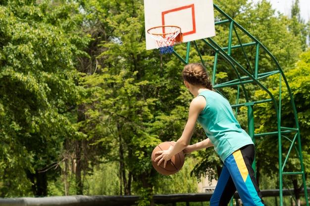 バスケットボールをするスポーティーなほっそりしたティーンエイジャー