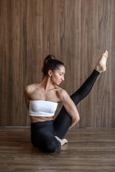 Sporty slender woman is engaged in stretching yoga in the gym