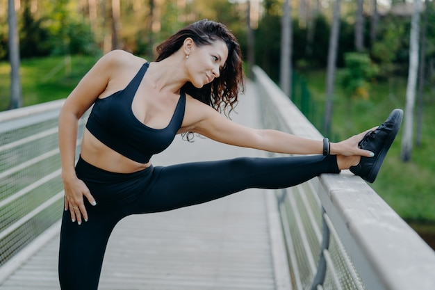 Sporty slim brunette woman dressed in cropped top and leggings stretches legs on bridge does warm up before morning run pose outdoor wants to have slim body and good health. workout