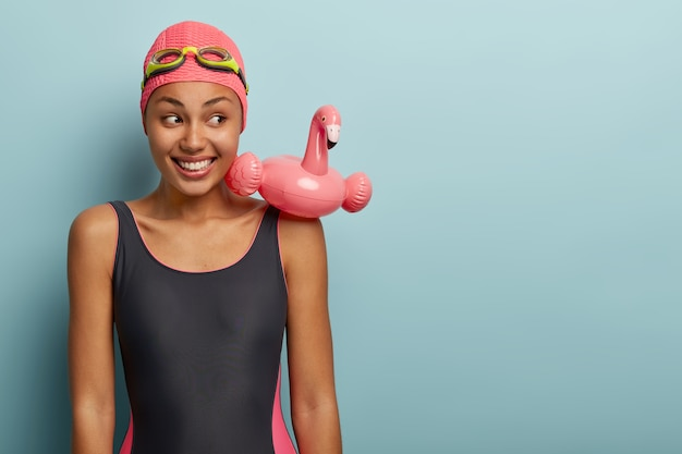 Sporty slim female with dark skin wears bathing suit, has swimming ring in shape of pink flamingo, goggles on head, spends free time in contemporary leisure center, ready for swim. active rest