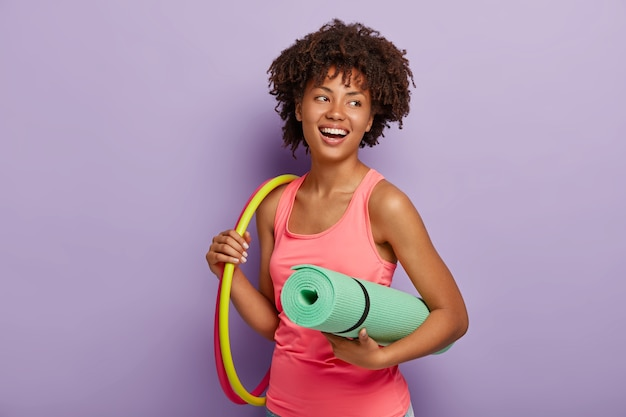 Sporty slim lady with healthy dark skin, afro hairstyle, exercises with hula hoop, carries rolled up mat, dressed in pink vest, has toothy smile