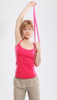 Sporty and slim woman`s workout with pink tape