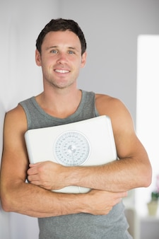 Sporty smiling man leaning against wall holding a scale