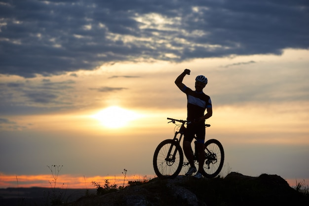 Sporty smiling man stands with bicycle on rock at top of hill