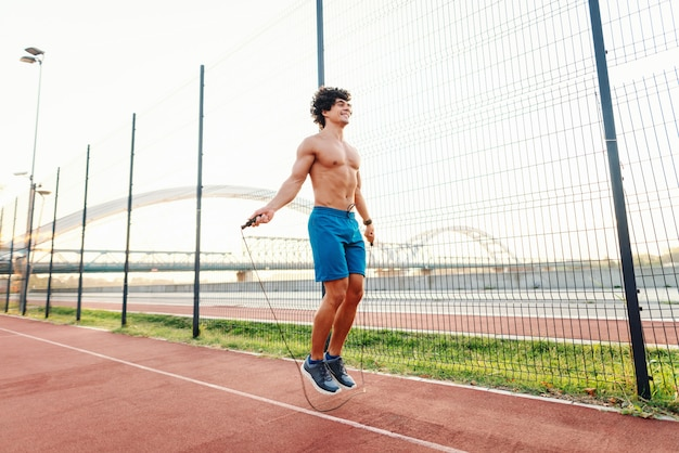 Sporty smiling shirtless man skipping rope in court in the morning next to wire fence