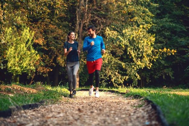 Во всю длину подходящих sporty счастливых кавказских пар в sportswear бежать в древесинах на следе в утре.