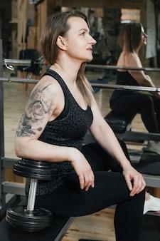 スポーティ強くて体にフィットするジムの女性、ウォーミングアップ。入れ墨のある中年女性パワーリフター。強くてフィットする体、健康的なライフスタイルのコンセプト。 40代の女性のトレーニングルーチンと持久力