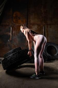 Спортивный тренер весело толкает шину