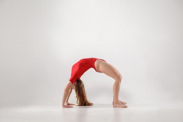 스포티한 여성은 다리 urdhva dhanurasana 요가 포즈를 하는 동안 손과 무릎으로 균형을 잡고 아치 형태로 뒤로 잡고 있습니다. 실내, 밝은 회색 배경입니다. 건강한 라이프 스타일과 여가 활동.