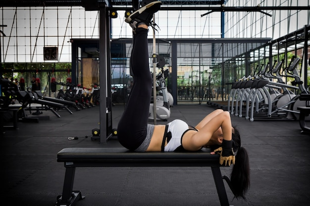 Sporty woman beautiful body doing legs raise on bench in fitness room.