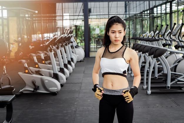 Sporty woman beautiful body in fitness room.