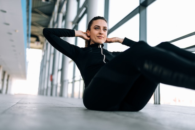 Sporty woman in black tracksuit doing sit-ups indoors.