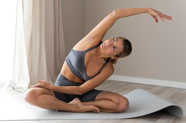 Sporty woman in blue fitness clothes stretching