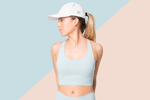 Sporty woman in blue sportswear and cap facing side