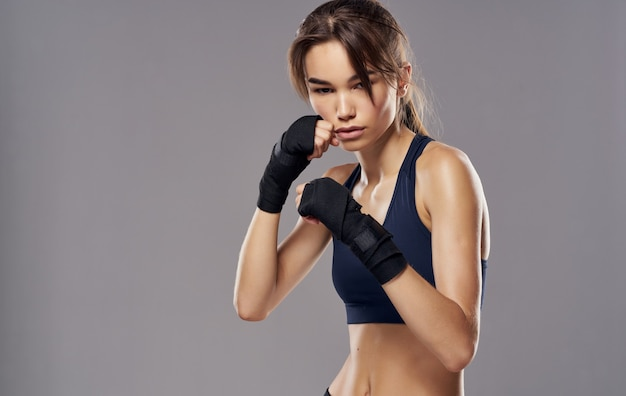 Sporty woman in boxing gloves on gray copy space.