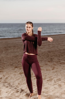 Donna sportiva dalla spiaggia che si estende