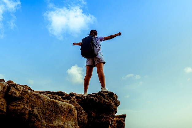 Sporty woman on the cliff. success and goal concept. strong and healthy for outdoor activity.