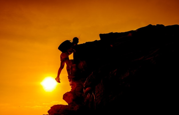 Sporty woman climbing on the cliff. success and goal concept. strong and healthy for outdoor activity. fresh start of day