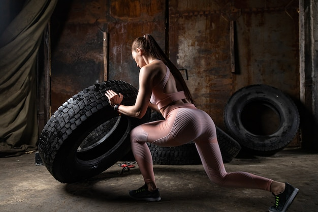 Sporty woman coach  doing fitness, pushing the tire in an old garage. fitness from a bodybuilder athlete in an incredible place