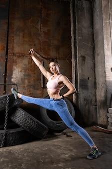 古いガレージで足を伸ばしてスポーティな女性コーチ。ボディービルダーアスリートの朝の体操、素晴らしい場所でのフィットネス