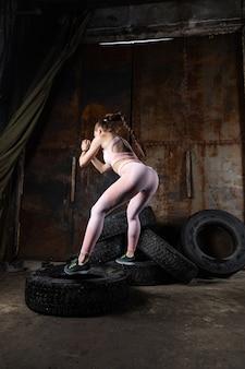 Спортивная женщина-тренер прыгает на шине, занимается фитнесом в старом гараже. концепция занятия спортом в сложных неподходящих условиях, замена специализированного спортивного инвентаря подручными средствами