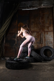 Sporty woman coach jumps on a tire, does fitness in an old garage. concept of playing sports in difficult inappropriate conditions, replacing specialized sports equipment with improvised means