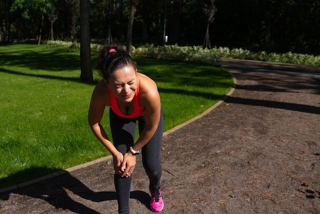 Sporty woman cramps in leg and feel pain. knee injury concept. joint inflamation