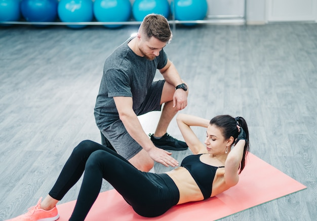 Sporty woman doing abs on the floor and a male trainer holding hand over her stomach in the gym.