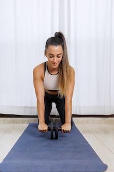 Спортивная женщина делает упражнения с колесом ab