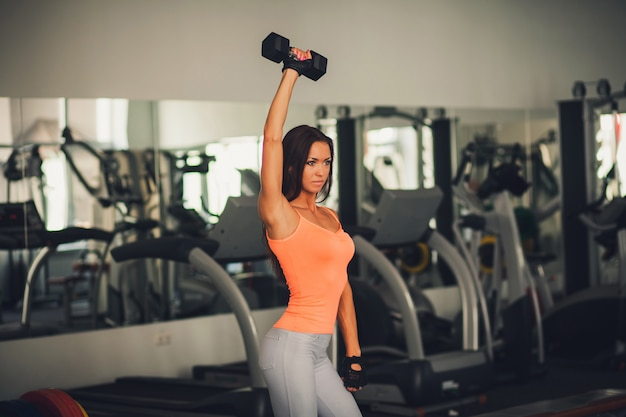 Sporty woman doing exercises with dumbbells