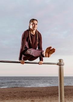 ビーチの外でフィットネスエクササイズをしているスポーティな女性